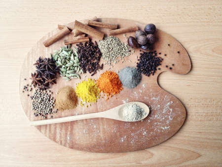 A lot of spices ingredient and wooden spoon on the paint palette. Stock Photo