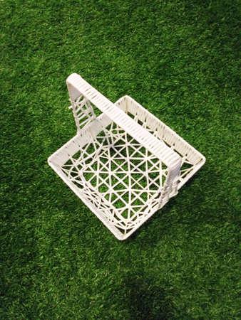 White basket in artificial grass