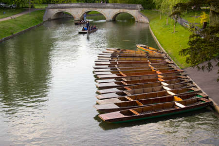 punting: Punting boats with names in a row docked in the river in Cambridge, UK Editorial
