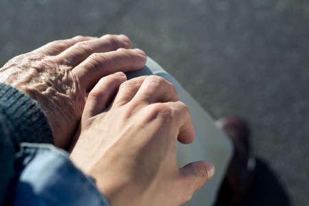 mano de un anciano y un joven entrelazadas encima de su pierna