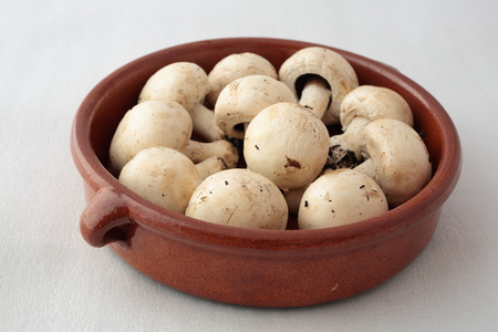 makro: clay pot with raw mushrooms with garlic and parsley