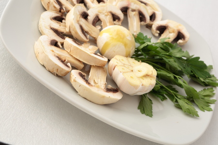 makro: plate of raw mushrooms with garlic and parsley