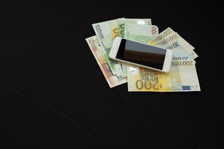 warrants: mobile phone and money on black background