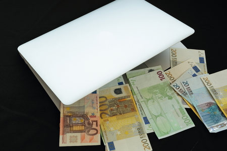 warrants: laptop with money on black background Stock Photo