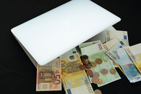 warrants: laptop with money on black background Stock Photo