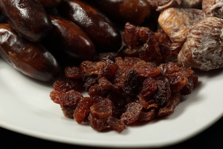 white plate with dried figs, dates and raisins Reklamní fotografie