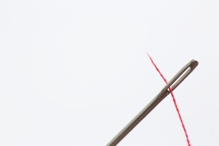 hilo rojo: aguja de coser a mano con la bobina hilo rojo