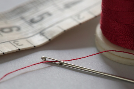 bobbin: hand sewing needle with red thread bobbin