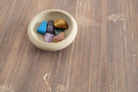 green tourmaline: mineral colors on a clay bowl on a wooden table Stock Photo