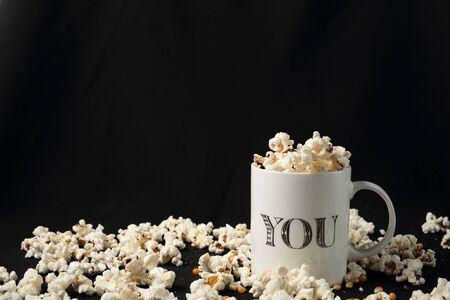 popcorn bowls: White jar with popcorn on black background Stock Photo