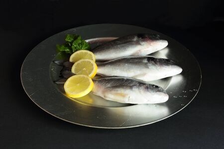 raw gold: gold raw fish on black background Stock Photo