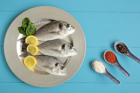 blue fish: raw fish on a blue background silver tray