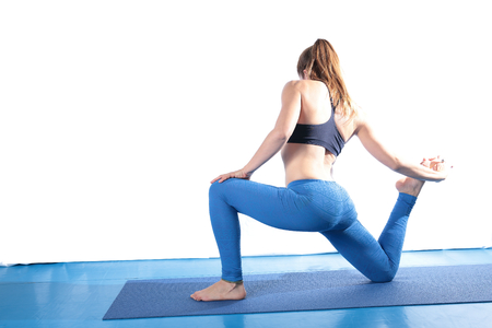 slim woman: Woman practicing yoga on the floor on a blue mat and white background