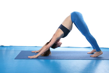 energy balance: Woman practicing yoga on the floor on a blue mat and white background