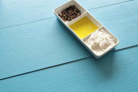 spay: Container with salt, oil and pepper on a blue wooden background