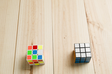 rubik: Elche, Spain. May 26, 2016: Two rubik cubes on a background of pine wood.