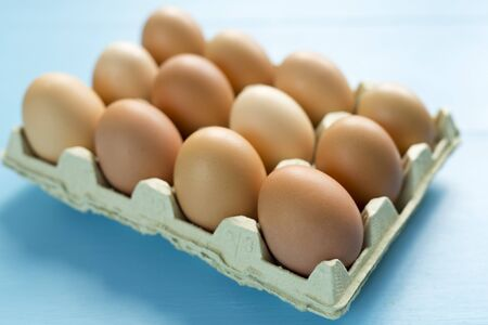 egg cup: Chicken eggs in an egg cup on a wooden background painted blue Stock Photo