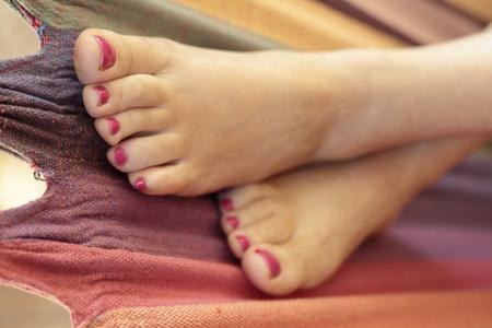 uñas pintadas: Pies de la mujer con las uñas pintadas descansando en una hamaca