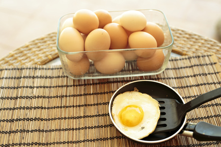 Fried egg in a small saucepan on a tablecloth Stock Photo