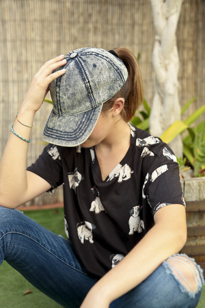 face covered: Girl with face covered with his Cap. Vertical capture. Stock Photo