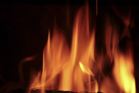 hotter: Flames of fire in a fireplace. Shooting horizontal with tones Orange and black.