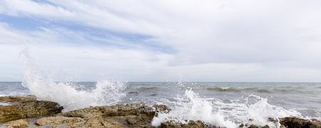 Rocky beach with waves in Santa Pola, Alicante province, Spain.
