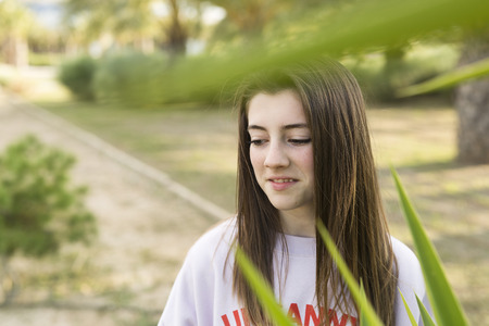 Portrait of a young 15 year old teenager between the plants of a park.