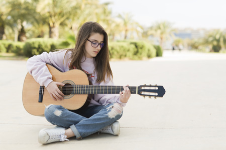 Portrait of a young 15 year old teenager sitting playing guitar in a park.