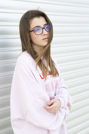Portrait of a young 15 year old teenager with glasses on a metallic background. vertical shot