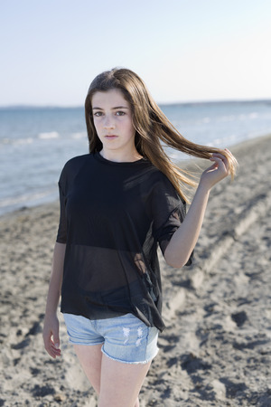 Young woman on a beach touching the hair of Santa Pola in Alicante province, Spain. Stock Photo