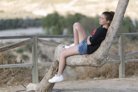 Teenage girl lying on top of a tree. Take place in Muxamel, province of Alicante, Spain.