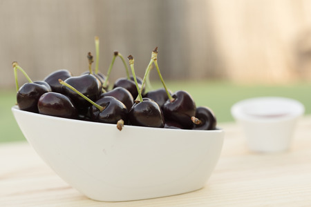 White bolw  with ripe cherries on a wooden background.
