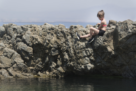 climbed: Girl climbed on some rocks of Tabarca Island, Alicante province, Spain