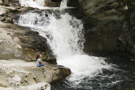 navarra: Girl sitting on a rock next to the Waterfall of the bucket in the Selva de Irati in Navarra, Spain. Stock Photo