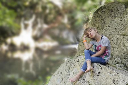 Meisjeszitting op een rots naast de Waterval van de emmer in Selva de Irati in Navarra, Spanje. Stockfoto