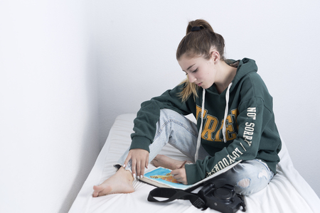 15 year old wearing a drawing sitting on her bed.