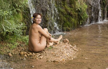 Woman of 40 years sitting without clothes in the river World in Lietor in the province of Albacete, Spain.