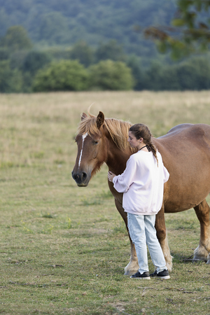 A teenager with horses in a meadow of Navarra, Spain.