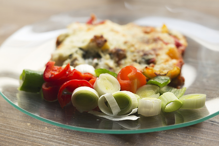 Vegetable lasagna in a glass dish on a wooden background. Stock Photo
