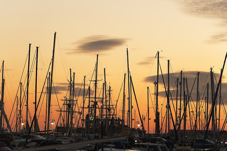 Masts of boats during a sunset in the port of Alicante, Spain. Foto de archivo