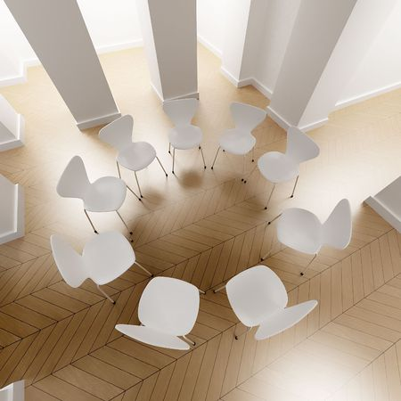 convention center: Aerial shot of a circle of white chairs in a room