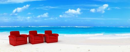 Three red club sofas in an idyillic beach of white sand and blue water Stock Photo - 2114208