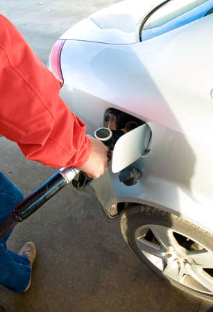 refilling: Man refilling his car�s tank with a gas pump