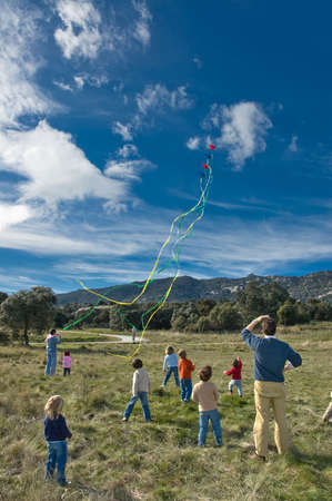flying kites: Some kids and parents watching a spectacular kite flying  Stock Photo