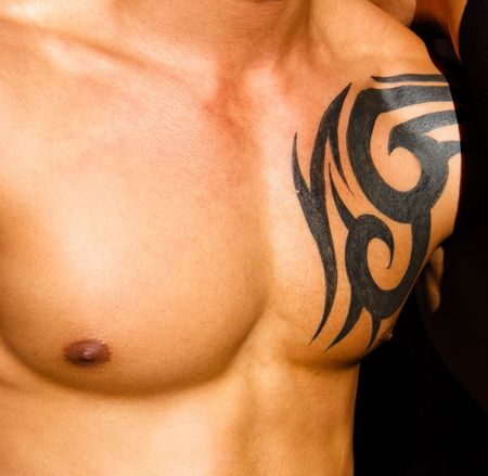 pectoral muscle: Male torso with tattoo with a dark background Stock Photo