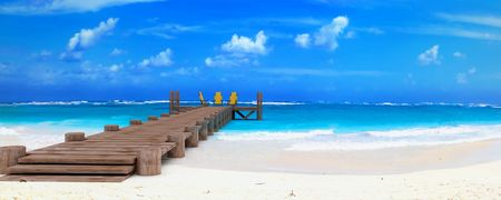 3D rendering of three deck chairs at the end of a wooden jetty at a tropical beach