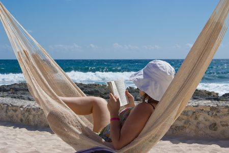 Woman reading in a hammock by the ocean photo