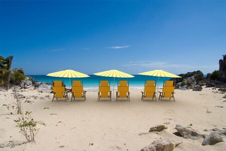 Tropical cove with white and yellow sunshades and reclining chairs Stock Photo - 4755570