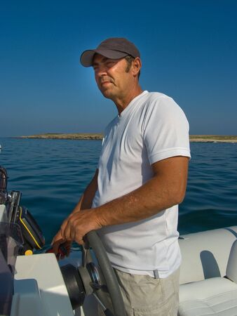 skipper: A man at the helm of his motorboat Stock Photo