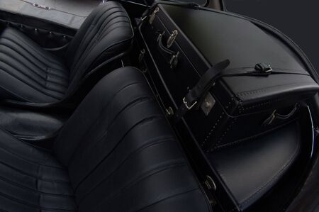 Backseat of a vintage car with retro luggage in the trunk photo